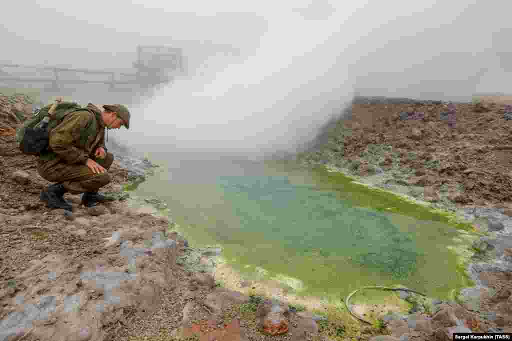 """A member of the expedition checks out a sulphur spring. As well as hunting for antique military leftovers, the team is also tasked with various """"botanical, volcanological, and geological"""" studies."""