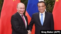 Russian President Vladimir Putin (L) and Chinese Premier Li Keqiang shake hands during a meeting in the Great Hall of the People in Beijing on June 8.