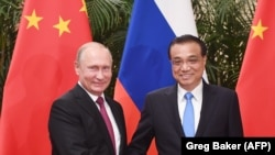 Vladimir Putin (solda) və Li Keqiang Pekində, arxiv fotosu