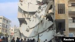 Орусиянын аба соккуларынан кыйрады делген Идлиб шаарындагы имараттардын жанындагы эл. Сирия, 20-декабрь, 2015-жыл