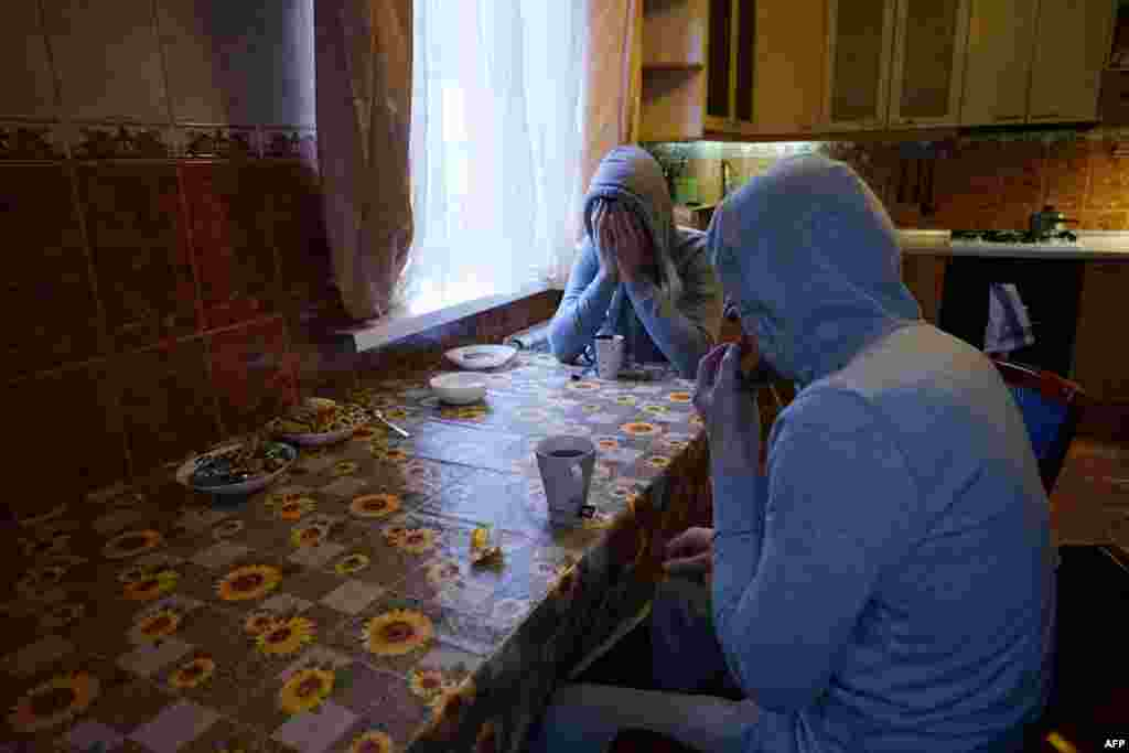 Chechen gay men, who fled persecution in the North Caucasus region, sit around a table in their flat in Moscow. (Naira Davlashyan)