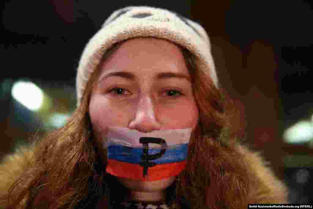 Активисты заклеивали рот российскими флагами со знаком рубля, держали «заляпанные кровью» плакаты с лозунгами, которыми сторонники упомянутых артистов и пророссийские деятели оправдывают их действия