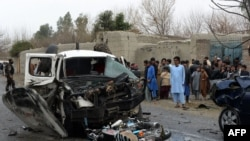 Bystanders look on as security force personnel inspect wreckage of vehicles at the site of a roadside rickshaw bomb explosion that targeted a senior local police vehicle in Behsood District of Nangarhar province on February 28.