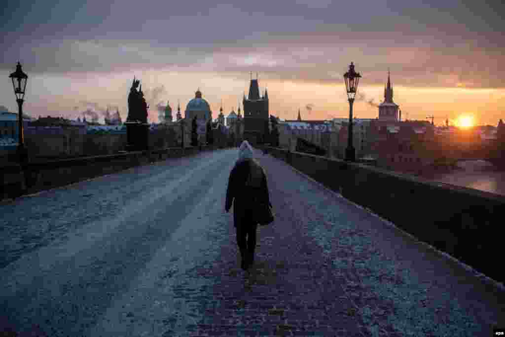 A woman walks across the Charles Bridge at sunrise during a freezing winter morning in Prague on January 11. (epa/Martin Divisek)