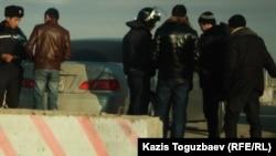 На блокпосту у въезда в Жанаозен полицейские сверяют лица и документы проверяемых с фотографиями и данными разыскиваемых по подозрению в участии в беспорядках в Жанаозене. 26 декабря 2011 года.