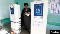 Shi'ite cleric Muqtada al-Sadr casts his vote at a polling station in Baghdad during parliamentary elections on April 30.