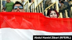 Fans of Iraq's national soccer team hold up the Iraqi flag in Irbil, the capital of the autonomous Kurdish region.