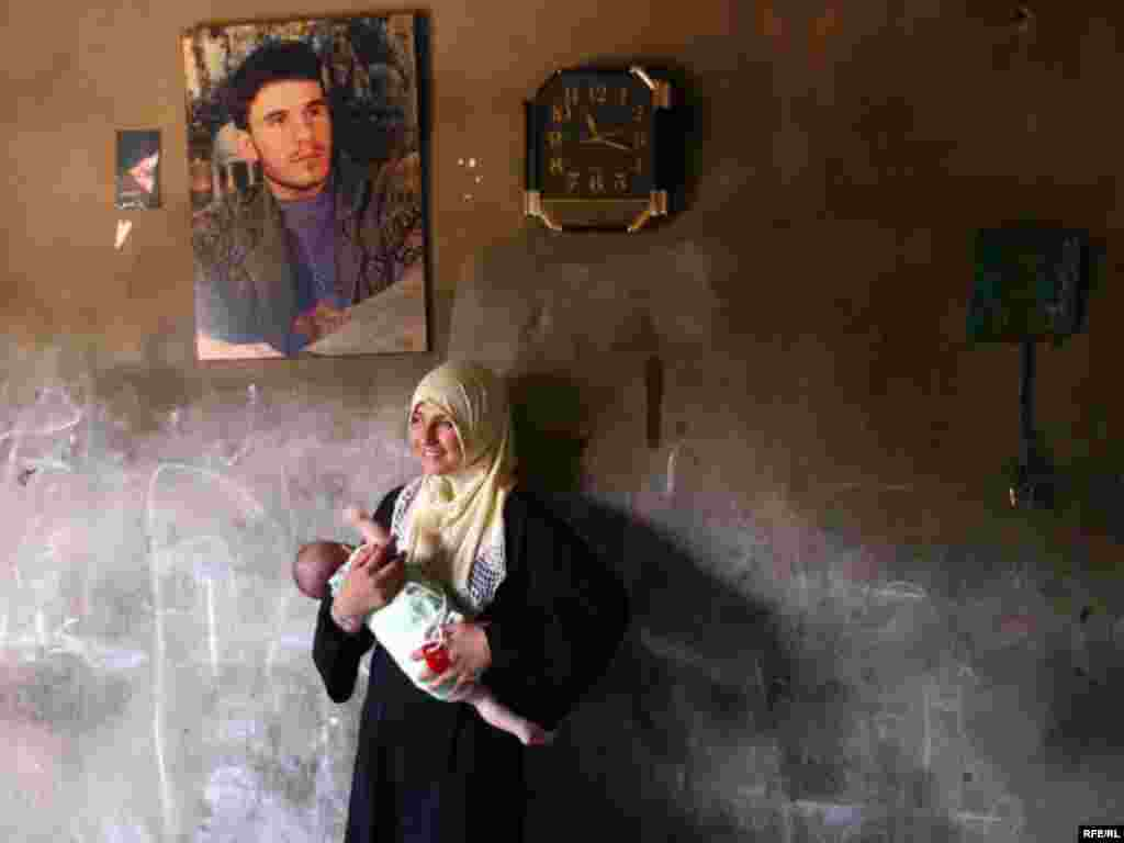 Lebanon, A mother and her baby with the picture of her husband who is a hizbullah supporter in Lebanon, undated