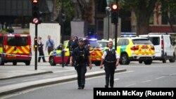 Полицейские у здания британского парламента после того, как там в ограждение врезался автомобиль. Лондон, 14 августа 2018 года.