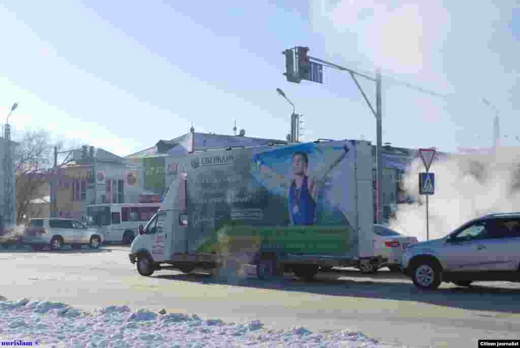 Реклама банка на автомобиле с изображением олимпийского чемпиона Серика Сапиева.