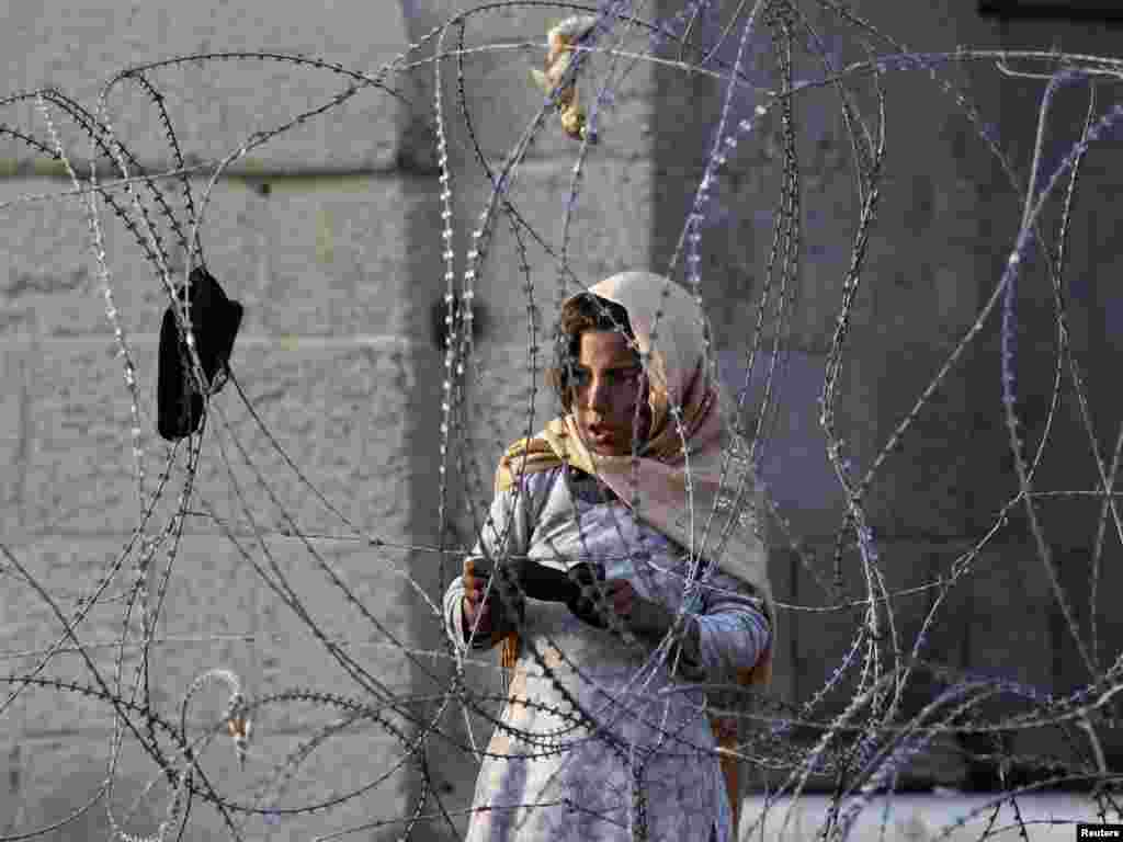 An Afghan girl looks on from behind barbed wire as Afghan forces investigate the site of a suicide attack in Kabul on November 12. A suicide car bomber attacked a NATO convoy near the new parliament building in the Afghan capital, police and the coalition said, the first attack in Kabul in three months after security was increased. Photo by Omar Sobhani for Reuters