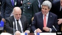 وزير الخارجية الاميركي جون كيري ورئيس الوزراء حيدر العبادي في بروكسل