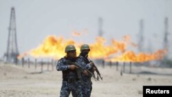 Flames burn off excess gas behind policemen standing guard at Zubair oil field in Iraq's southern province of Al-Basrah in late June.