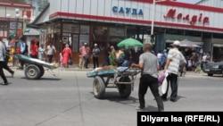 Базар маңында арба сүйреген адамдар. Түркістан