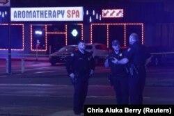 """Полициячылар каргашалуу окуялардын бири орун алган """"Голд Спа"""" массаж салонунун сыртында сүйлөшүп турушат. Атланта, Жоржия штаты, АКШ. 2021-жылдын 16-марты."""