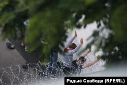 Затрыманыя пратэстоўцы стаяць ля сьцяны ў двары Савекага РУУС Менску. 14 ліпеня 2020