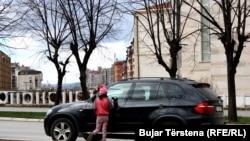 Një vajzë duke pastruar xhamat e një automjeti në Prishtinë