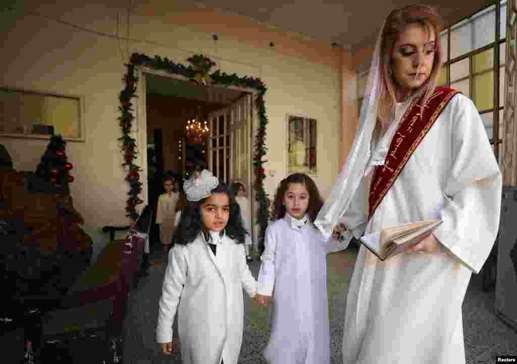 СИРИЈА - Сиријска христијанка со децата учествува во црковното чествување на Божиќ во Сириската православна црква во градот Камишли. Христијаните во Сирија, покрај божиќните празници, славеле и поради одлуката на Русија да воспостави постојано присуство на сили на нејзините две воени бази во Сирија: руската поморска база во Тартус и во воздушната база во Латакија.