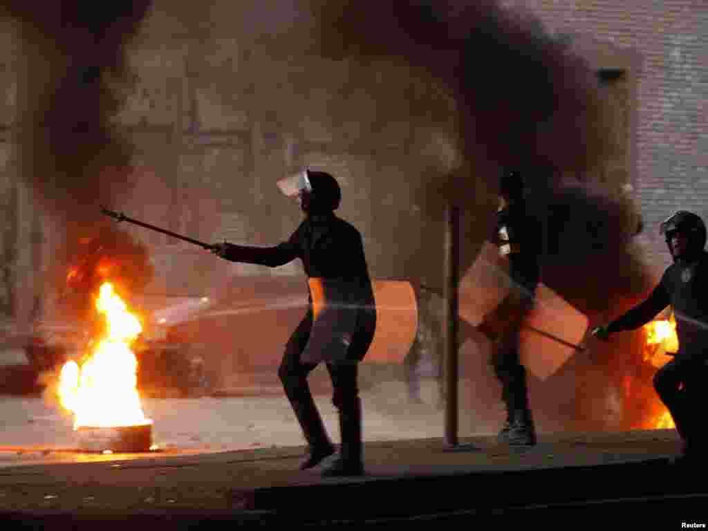 Riot police walk past a burning barricade during clashes in Cairo on January 26.