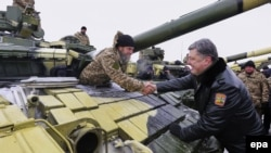 Ukrainian President Petro Poroshenko (right) greets soldiers at a military base in the eastern Ukrainian town of Chuguyev, in the Kharkiv region, on December 6.