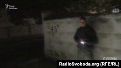 Чоловік у цивільному направляє пістолет на журналістів