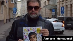Российский музыкант Борис Гребенщиков держит в руках фотографию узбекского заключенного журналиста Мухаммада Бекжана.
