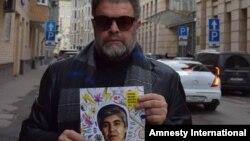 Ресейлік музыкант Борис Гребенщиков қамаудағы өзбек журналисі Мұхаммед Бекжанның портретін ұстап тұр.