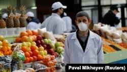 Торговец в маске на одном из рынков в Алматы.