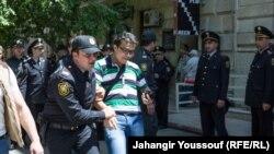 Полицейские задерживают активиста, вышедшего на акцию протеста. Баку, 6 мая 2014 года.