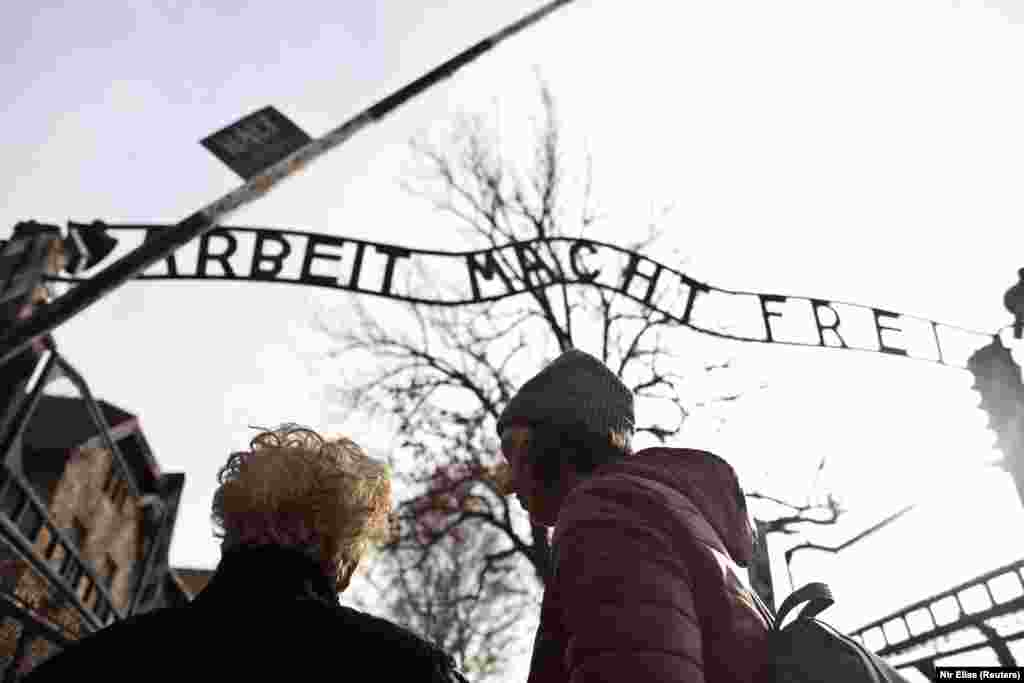 "Jona Laks, survivor of Auschwitz concentration camp, and her granddaughter, Lee Aldar stand next to the gate with the slogan ""Arbeit macht frei"" (""Work sets you free"") as they start their visit at the Auschwitz death camp in Oswiecim, Poland January 26, 2020."