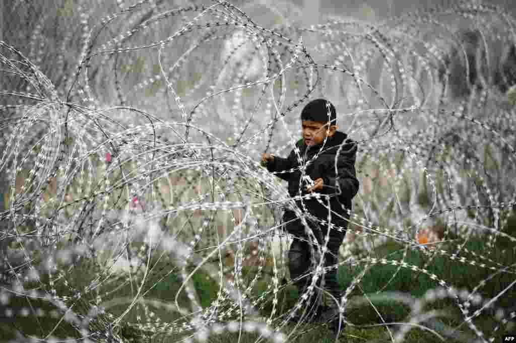 A child stands in a razor-topped fence close to the gate at the Greek-Macedonian border near the Greek village of Idomeni. (AFP/Dimitar Dilkoff)