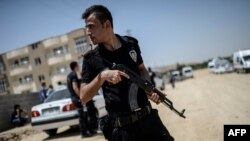 Турецький правоохоронець у місті Сейланпінар поблизу будівлі, де знайшли вбитими двох поліцейських, 22 липня 2015 року