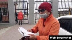 Жительница Кызылорды Акжан Ногаева читает стихи у здания акимата Кызылординской области. Кызылорда, 1 апреля 2020 года.