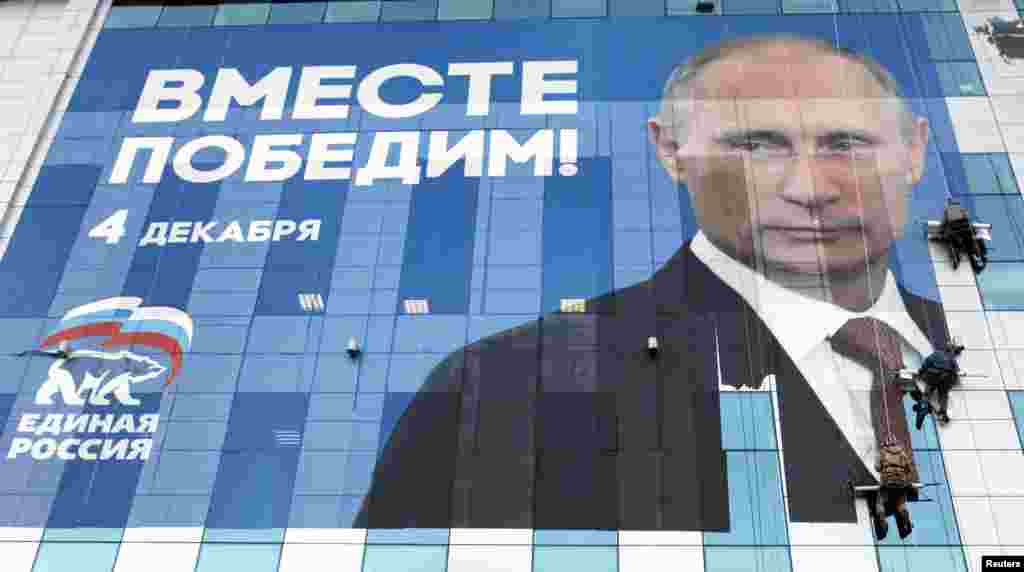 Workers attach an election poster featuring Prime Minister Vladimir Putin, appealing to people to vote for the United Russia political party, onto an office building in the southern city of Krasnodar late last year.