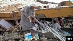 رجل يتفحص أنقاض مدرسة مدمرة في قرية قرب تكريت