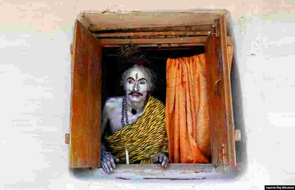 A devotee dressed as the Hindu god Shiva looks out from a window as he waits to perform during the annual Shiva Gajan religious festival on the outskirts of Agartala, India. (Reuters/Jayanta Dey)
