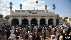 In this file photo, people gather outside a mosque in Nowshera after a bomb exploded there in March 2011.