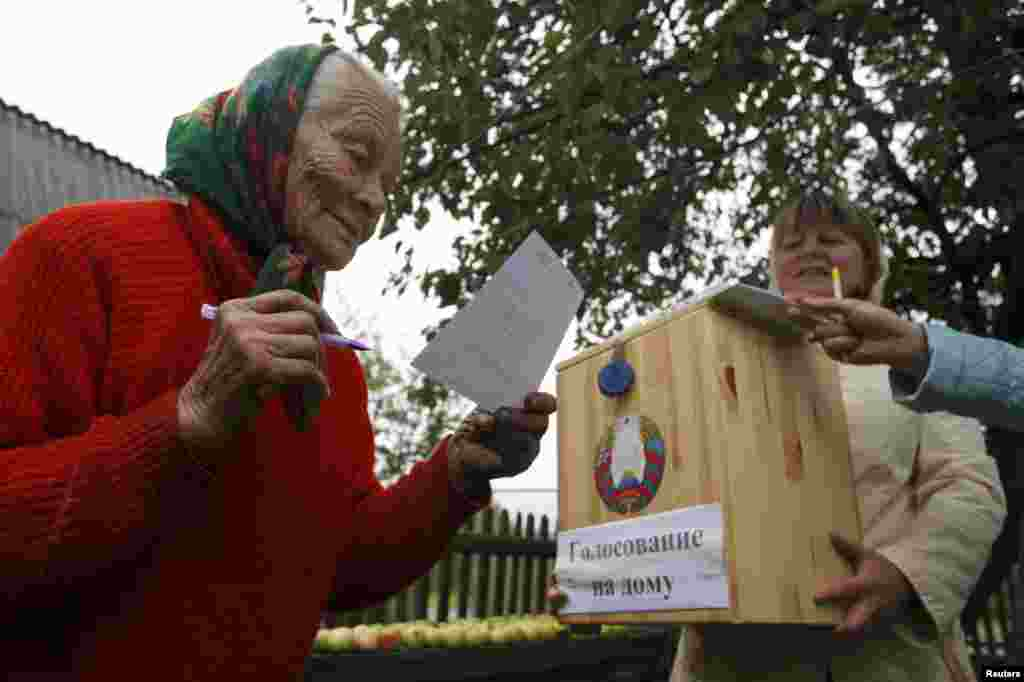 A woman reads a ballot before casting her vote into a portable ballot box in the village of Slobodschina.