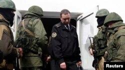 Украин офицери штабдан куралчан адамдардын коштоосунда чыгып баратат, Севастополь, 19-март, 2014