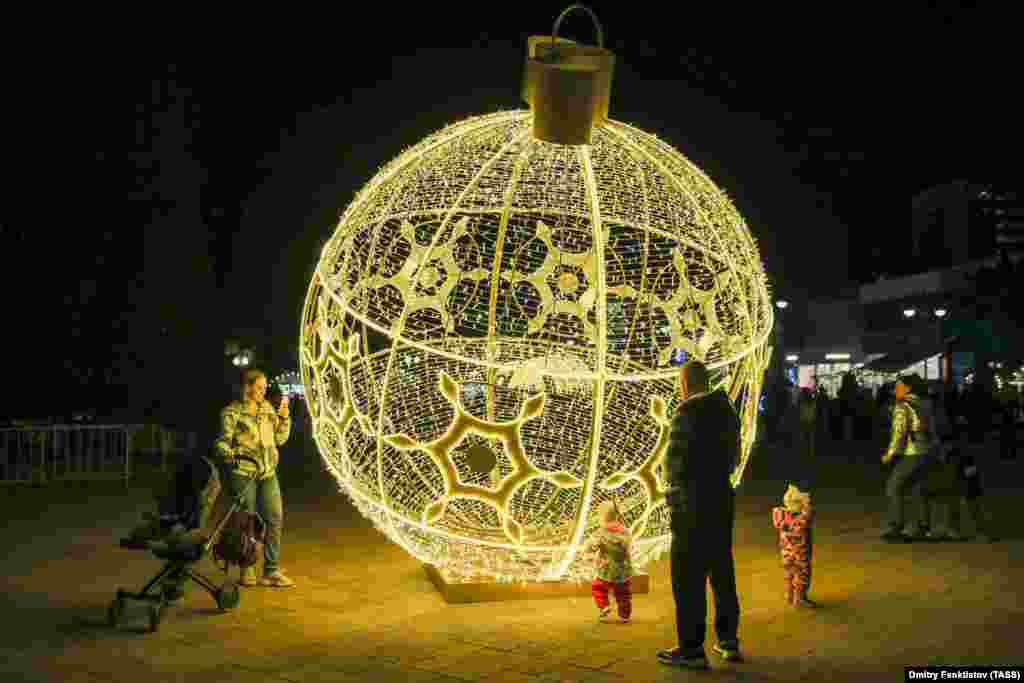 Egy túlméretezett karácsonyfadísz bevilágítja Szocsi egyik utcáját.