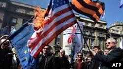 Vojisllav Sheshel dhe përkrahësit e tij, duke djegur flamurin amerikan dhe atë të BE-së, në përvjetorin e bombardimeve të NATO-s, 24 mars 2015, Beograd