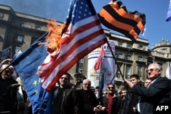 Seselj (right), surrounded by his supporters, holds a burning U.S. flag during an antigovernment rally in Belgrade on March 24.