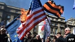 Vojisllav Shesheli duke e mbajtur flamurin amerikan që digjet në përvjetorin e 16-të në bombardimeve të NATO-s kundër caqeve serbe në Kosovë dhe Serbi