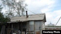 """Полуразрушенный дачный домик на фоне президентского дворца """"Акорда"""". Астана, июнь 2011 года."""