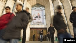 Назарбаев портреті ілінген Ұлттық музейден шығып келе жатқан студенттер. Алматы, 28 қараша 2012 жыл.