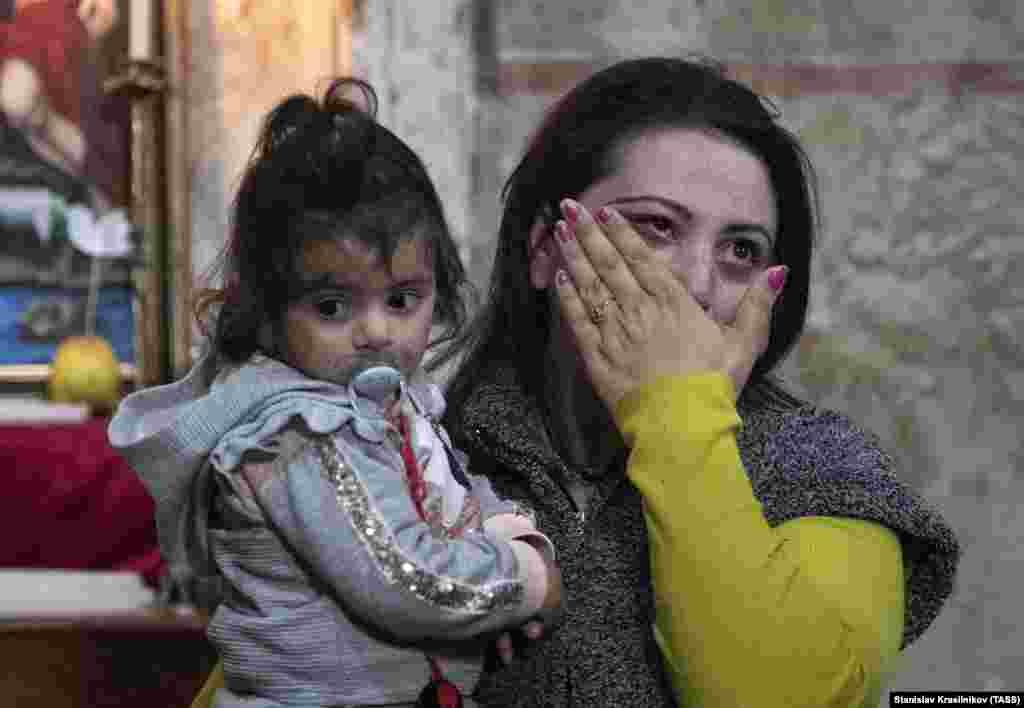 A woman wipes away tears as she walks inside the monastery with her daughter.