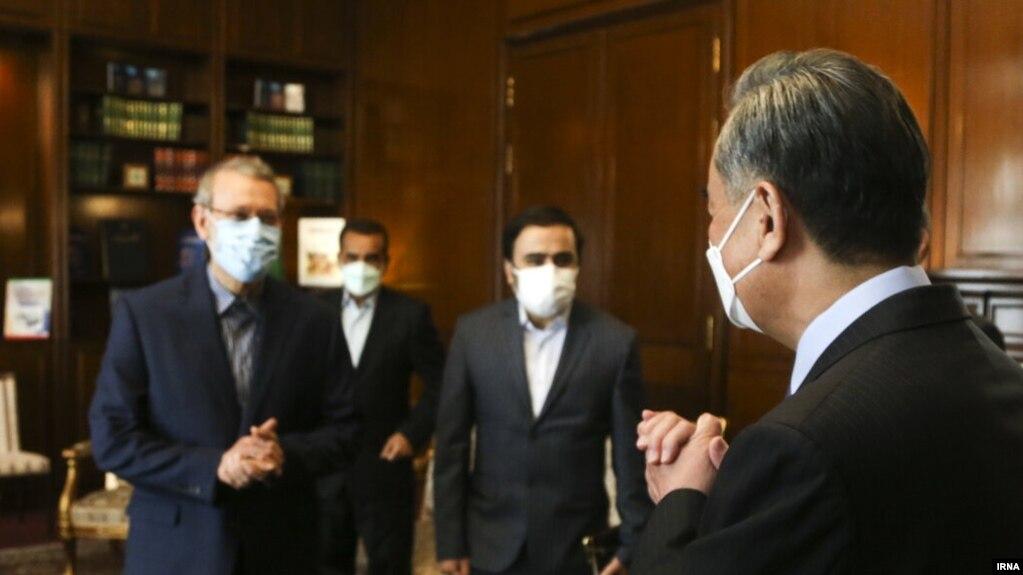 وانگ یی (راست) در دفتر کار علی لاریجانی