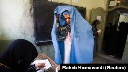 Egy nő azonosítja magát az országgyűlési választásokon, hogy leadja szavazatát 2010. szeptember 18-án Herátban.