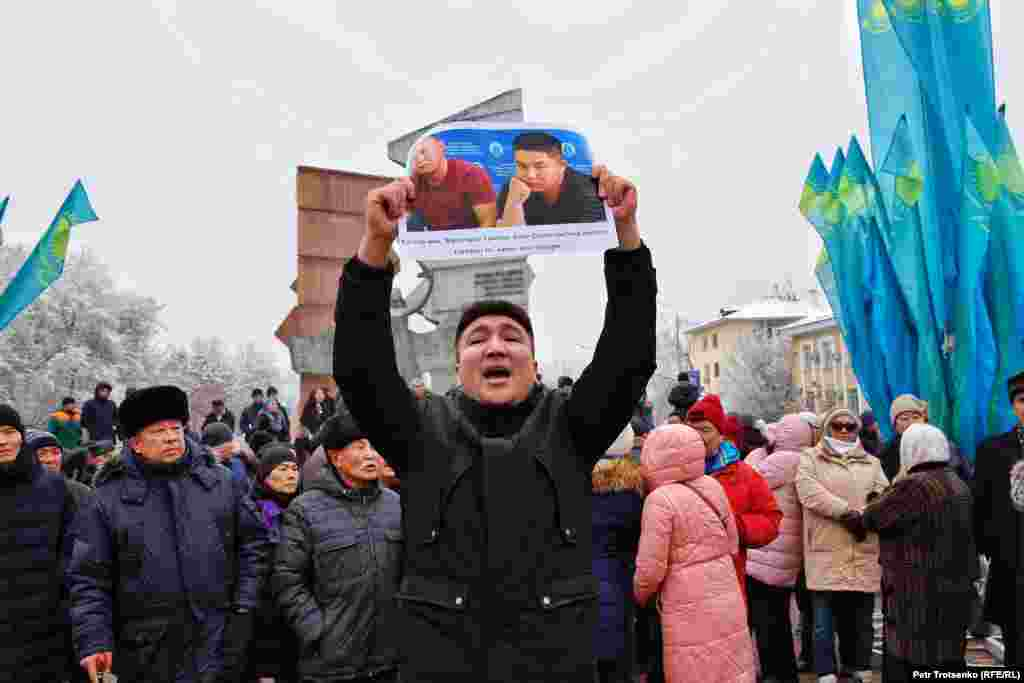 """A man in Almaty holds a photo of two ethnic Kazakhs from China facing deportation back to China where many fear they may be sent to """"re-education camps""""."""