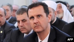 Syrian President Bashar al-Assad sits during a prayer to mark the birth of Islam's Prophet Muhammad in Damascus on January 24.